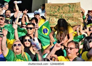 "São José dos Campos, São Paulo / Brazil - 10/21/2018 - People vibrating and a poster written behind: ""Brazil above all, God above all"" at the Pro Bolsonaro demonstration for President"
