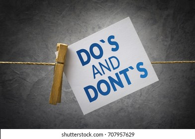 Do`s and don`ts paper note attach to rope with clothes pins on dark background