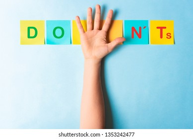 Do's and don'ts sign with multicolored sticky notes and a palm of hand showing 5 fingers on blue background