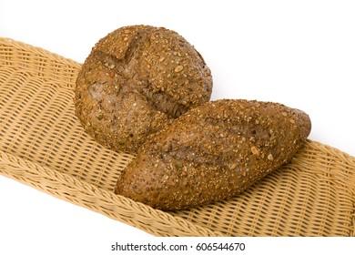 Dos panes oscuros con semillas sobre cesta de mimbre y fondo blanco