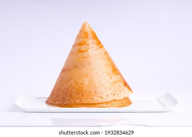Dosa _Ghee roast Dosa_cone shaped dosa,famous south Indian breakfast item which is made in caste iron pan in traditional way and arranged on a white base ,on a white background ,isolated.