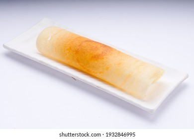 Dosa _Ghee roast  Dosa,famous south Indian breakfast item which is made in caste iron pan in traditional way and arranged on a white tableware on a white background ,isolated.