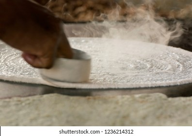 Dosa batter being spread on tawa