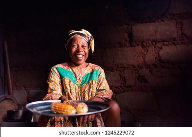 Douala Cameroon - 06 august 2018: closeup of old african lady in her rural home kitchen with traditional dress looking in camera offering food