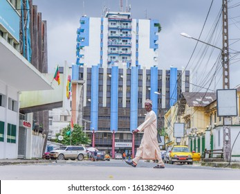 Douala / Cameroon - January 12 th 2020. A man crossing the street, with a blue and white building behind with Cameroon flag in the very heart of Douala,