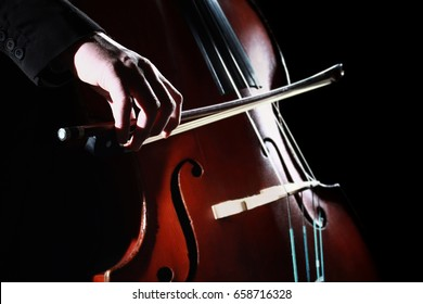 Double bass player Hands playing contrabass musical instrument.