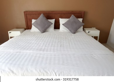 Double bed in the bedroom interior with white and gray pillows and white cloth and brown wall.