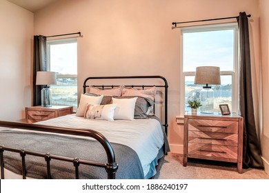 Double bed between single hung windows and lampshades on top of side tables