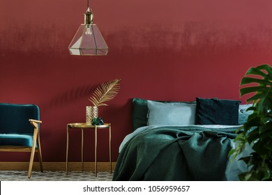 Double bed with emerald sheets and gold side table with leaf decoration in bedroom interior