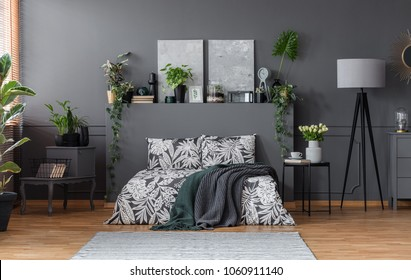 Double bed with floral bedding and dark blankets standing in grey bedroom interior with fresh plants, paintings and lamp