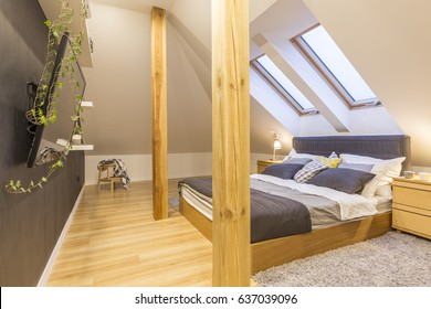 Double bed in stylish wooden bedroom in the attic