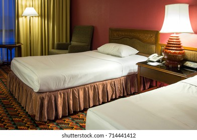 Double bed with table lamp in the bedroom at night time