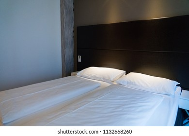 Double bed with white sheet in dark tone room.