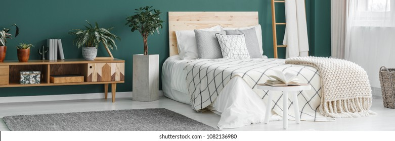 Double bed with wooden bedhead standing in green room interior with fresh plants and grey carpet