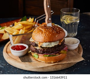 Double beef burger with egg, with fried potatoes and sauces on the table