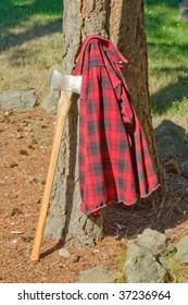 Double Bit Axe in Stump with Red Black Flannel Shirt Hanging on Handle. A pile of wood is next to the stump.