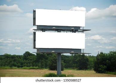 Double blank white  Billboards, one above the other, alongside highway with trees and partly cloudy sky as background.