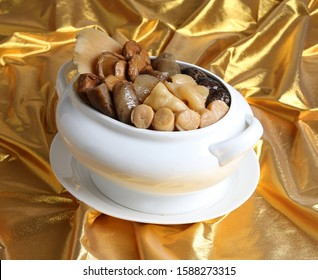 double boiled buddha jump over the wall chinese herbal soup with premium dry seafood in gold background for chinese new year