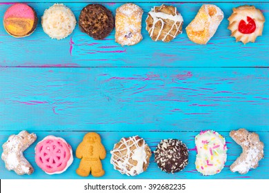 Double border of colorful cookies or biscuits arranged in a line on a turquoise blue crackle paint wooden background, overhead view with copy space
