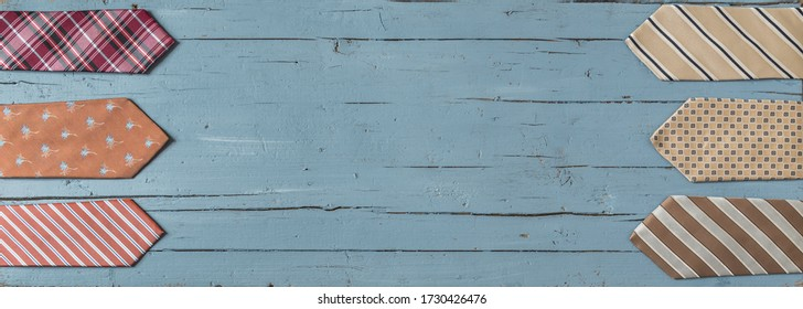 Double border of colorful ties on a light blue wooden background with copy space.