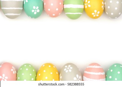 Double border of hand painted pastel Easter eggs over a white background