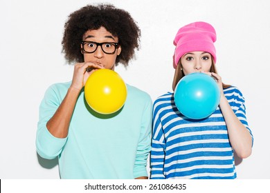 Double bubble love. Funky young couple inflating balloons while standing against white background