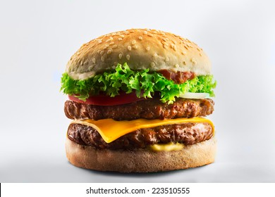 Double burger with cheese, tomato and lettuce on white table against white background.
