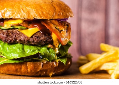 Double Burger on the board on wooden background. Huge double burger on a wooden board on a wooden background. with french fries close