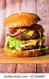 Double Burger on the board on wooden background. Huge double burger on a wooden board on a wooden background. in the center
