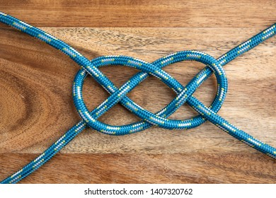 Double Carrick Bend on wooden background. Rope knot