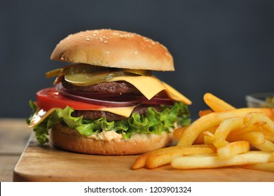 Double cheeseburger and french fries on a light wooden table. Burger filling consists of two steaks, vegetables, cheese and sauce. Dark background. Close-up. Macro shooting.