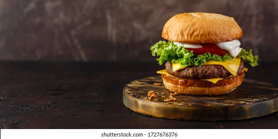 Double cheeseburger with lettuce, tomato and melted cheese on wooden board. Long wide banner