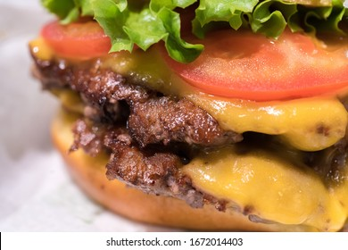 Double cheeseburger with tomato lettuce and onion, Cheese Fries and Milkshake.