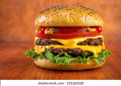 Double cheeseburger with tomato, onion, mustard and ketchup, poppy seeds on top bun , on red wooden table
