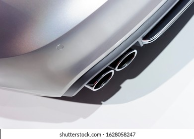 Double chrome exhaust pipe of sport car with silver metallic bodywork, automobile industry, selective focus