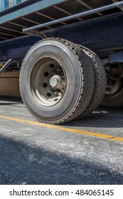 Double construction truck wheel side perspective angled weathered and worn rubber tyre