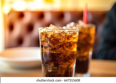 Double cool ice soft drink cola carbonated liquid fresh food with soda water, white dish on wooden table with handsome man sitting  brown sofa in pizzeria restaurant.