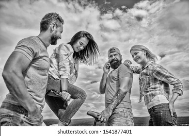 Double date concept. Group friends hang out with bicycle. Company stylish young people spend leisure outdoors sky background. Cycling modernity and national culture. Couple meet friends with bicycle.