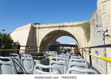 A double Decker bus tour through Europe on a Sunny day.