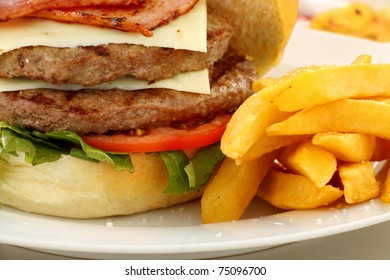 Double decker hamburger with bacon and cheese and golden fries.