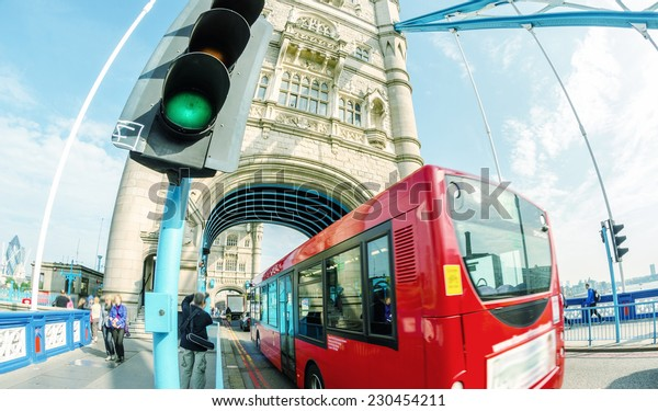 Double Decker red bus crossing Tower Bridge.