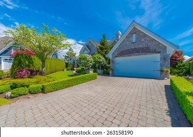 Double doors garage with nicely paved wide, long driveway. North America. Canada.