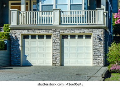 Double doors garage with wide, long driveway.