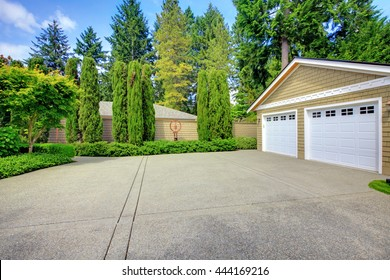 Double doors garage with wide, long driveway and lots of greenery. North America.