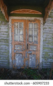 Double doors of an old wooden house. The paint on the door was peeling off.
