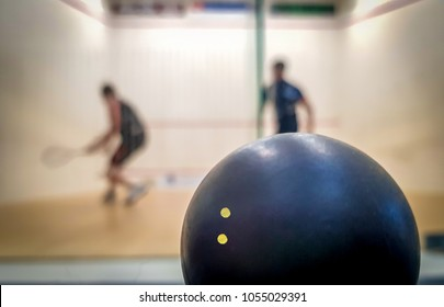 Double dot squash ball with two players in the background