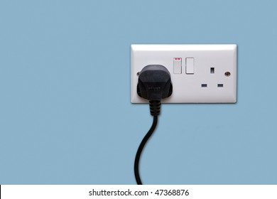 Double electrical power socket and single plug switched on, blue background.