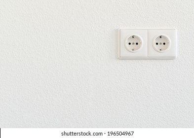 double electrical socket on white wallpaper
