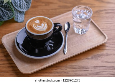 Double Espresso Macchiato in Black Cup and Saucer with Glass of Water, Spoon on a Wooden Table and Wooden Floor