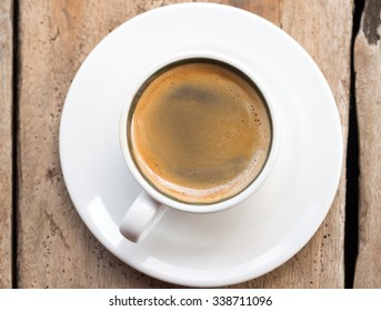 Double espresso in a white cup placed over a dhow wood table. Elevated view, vertical orientation. Elevated view.